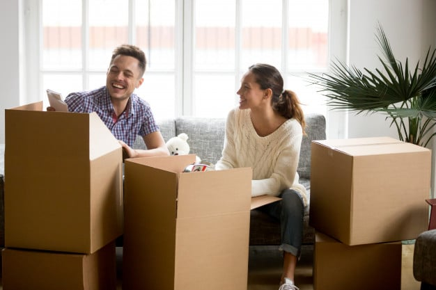 Couple laughing while unpacking from cardboard